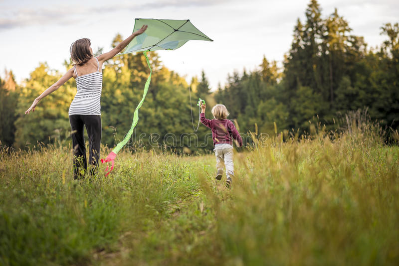 帮助她的孩子的年轻母亲飞行风筝 免版税库存照片
