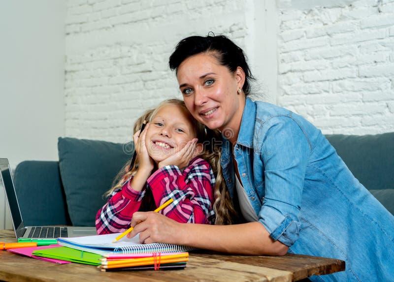 帮助她的年轻白肤金发的逗人喜爱的甜女孩的美丽的母亲在家做家庭作业在家庭作业育儿和教育概念 库存图片