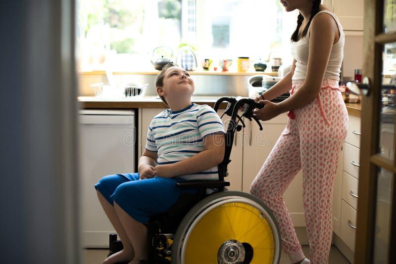 帮助她的残疾兄弟的姐妹在厨房里 库存照片