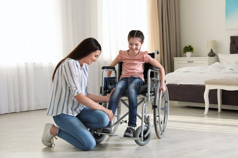 帮助她的残疾女儿的年轻女人得到在轮椅 免版税图库摄影