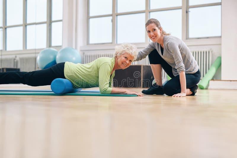 帮助她的锻炼的健身房教练年长妇女 库存照片
