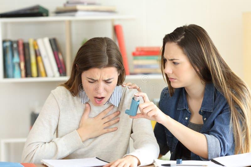 帮助她的asmathic朋友的学生 库存图片