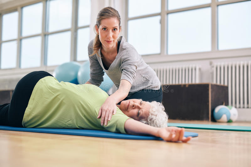 帮助她舒展的锻炼的教练员资深妇女 免版税库存照片