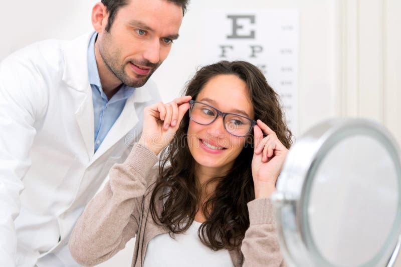 帮助妇女的眼镜师选择玻璃 免版税库存照片