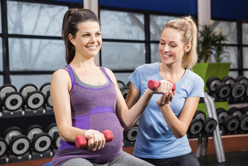 帮助孕妇的教练员在健身房 免版税库存照片
