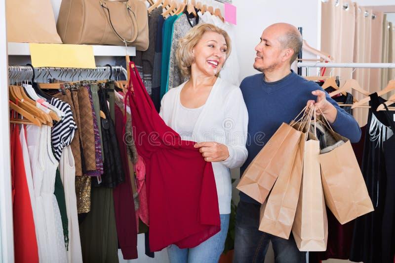 帮助宜人的妻子的微笑的资深丈夫选择礼服 免版税库存照片