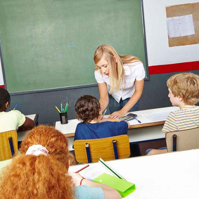 帮助小学学生的老师 图库摄影