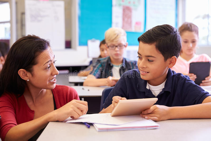 帮助小学男孩的老师使用片剂计算机 免版税库存照片