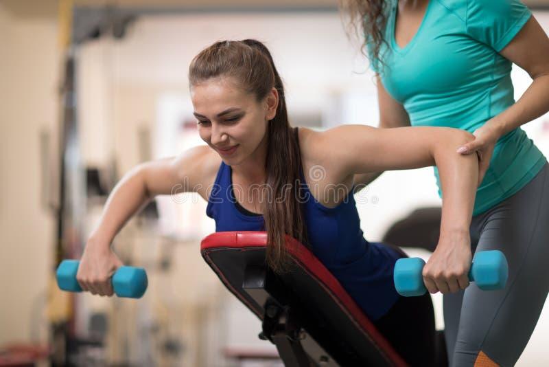 帮助少妇用重量在健身房的训练器材的个人教练员 免版税库存图片