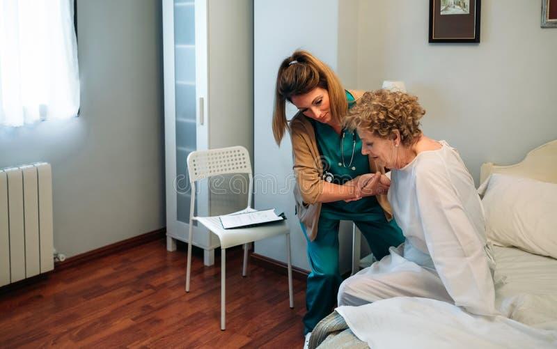 帮助年长患者的照料者下床 免版税库存图片