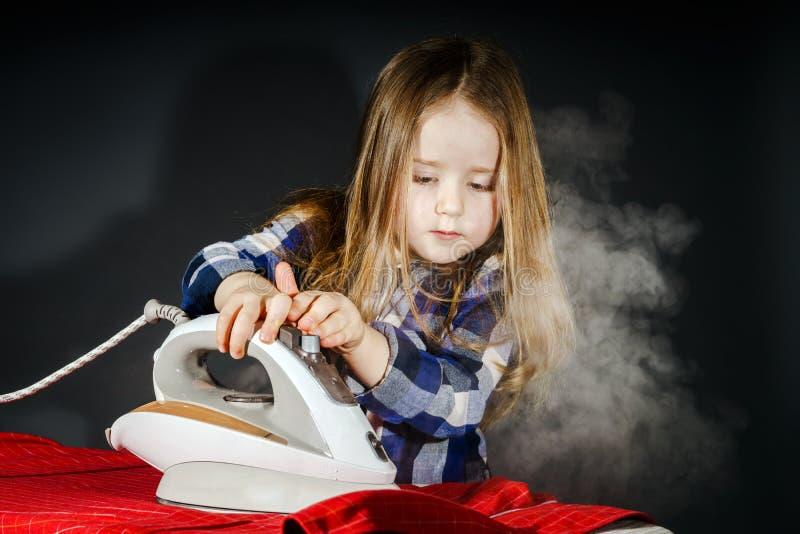 帮助您的母亲的逗人喜爱的小女孩通过电烙衣裳,反对 免版税库存照片
