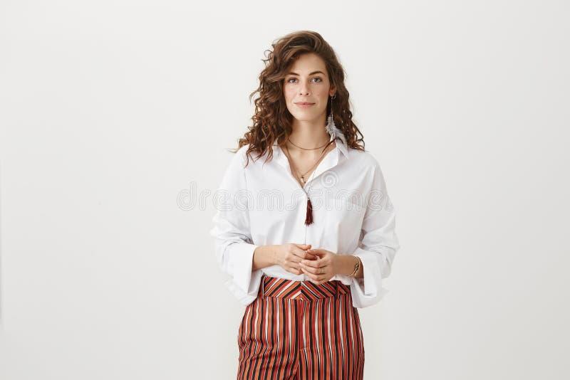 帮助我如何可以您 演播室射击了与时髦的卷曲理发的时兴的成年女性,站立在花梢成套装备  免版税库存照片