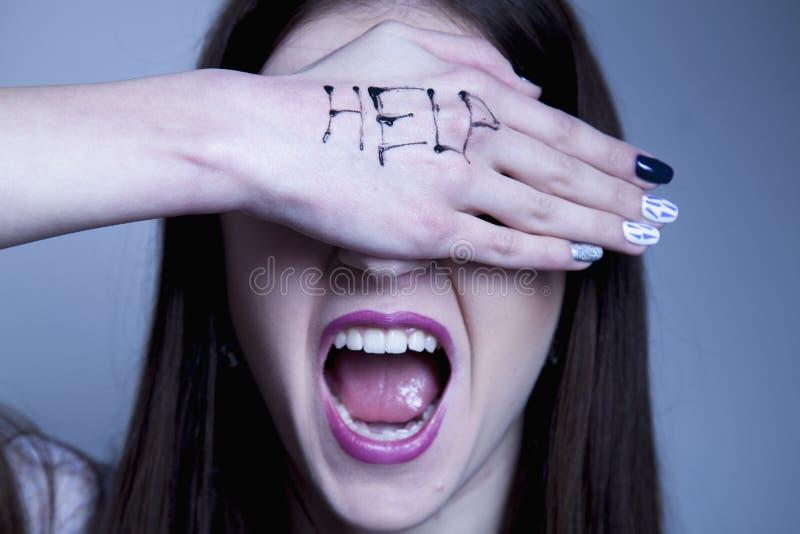 帮助我!妇女` s求救与被绘的题字的在她 库存图片