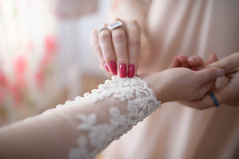 帮助新娘的女傧相或伴娘按有花边的被绣的长袖她的礼服 免版税库存图片