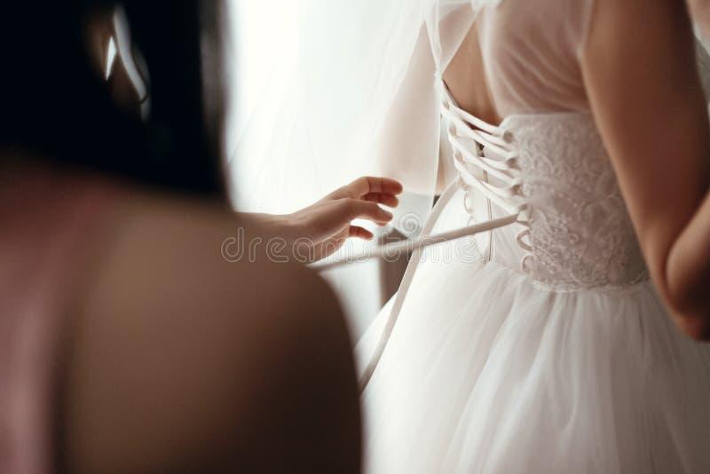 帮助新娘的女傧相换衣服在婚礼服, getti 免版税库存图片