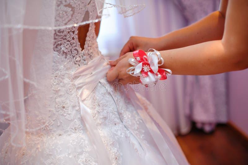 帮助新娘的女傧相穿一套白色婚礼礼服 库存图片