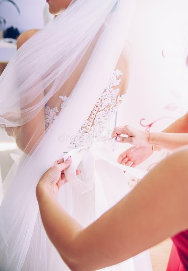 帮助新娘的女傧相穿戴在她的豪华婚礼礼服早晨在庆祝前 图库摄影