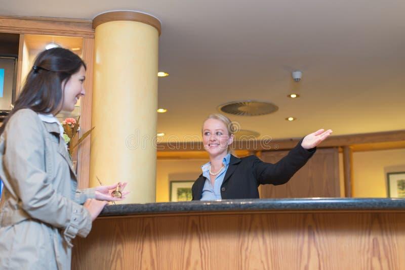帮助旅馆客人的微笑的接待员 库存照片