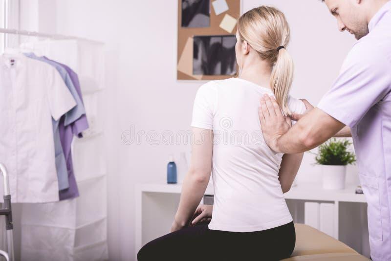 帮助有一块弯曲的脊椎的生理治疗师患者 库存照片
