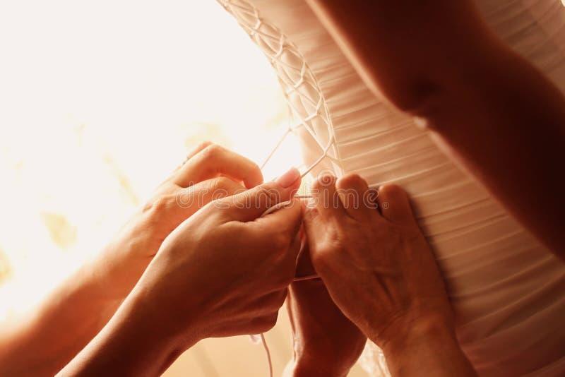 帮助有她的婚礼礼服的手新娘 图库摄影