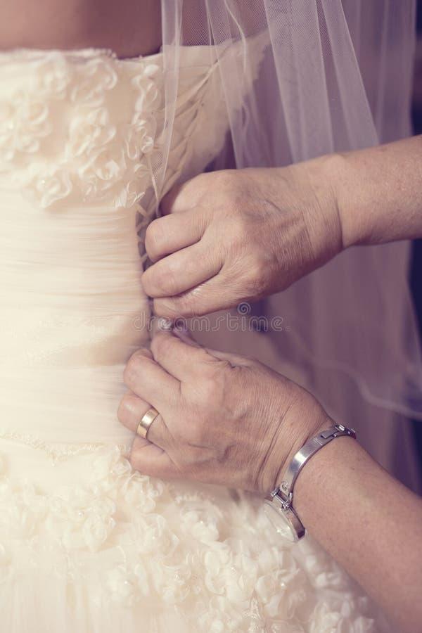 帮助有婚礼礼服的母亲新娘 免版税库存图片