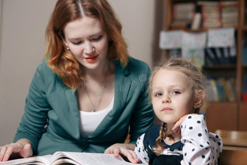 帮助有家庭作业的女性私人教师年轻学生在书桌在明亮的儿童` s室 免版税库存照片