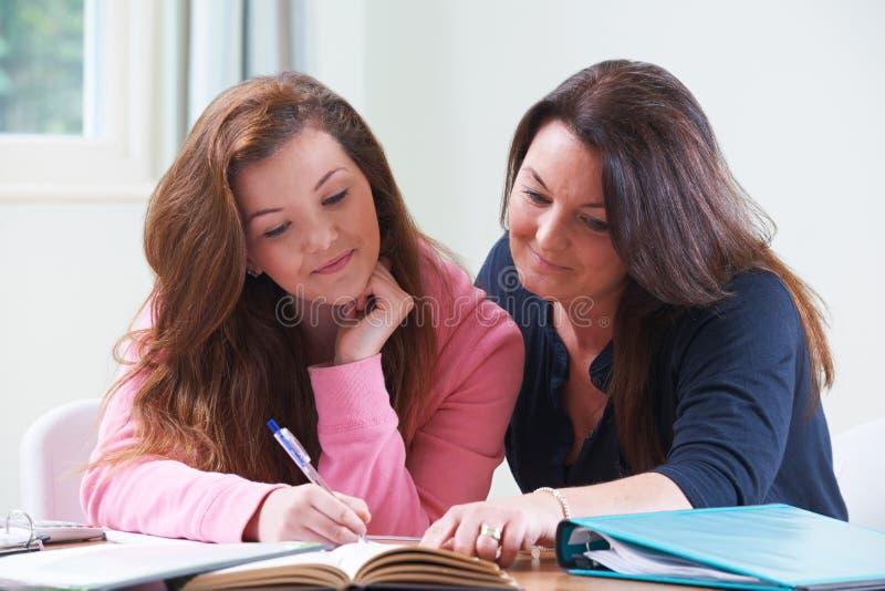 帮助有家庭作业的母亲十几岁的女儿 库存图片