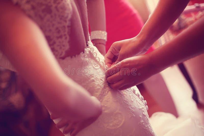 帮助有礼服的手新娘 免版税库存图片