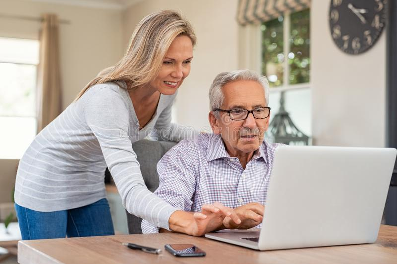 帮助有膝上型计算机的女儿老父亲 免版税图库摄影