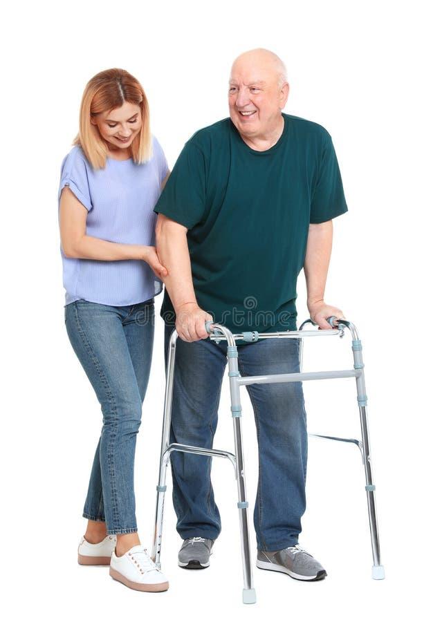 帮助有走的框架的看守者年长人在白色 免版税库存照片