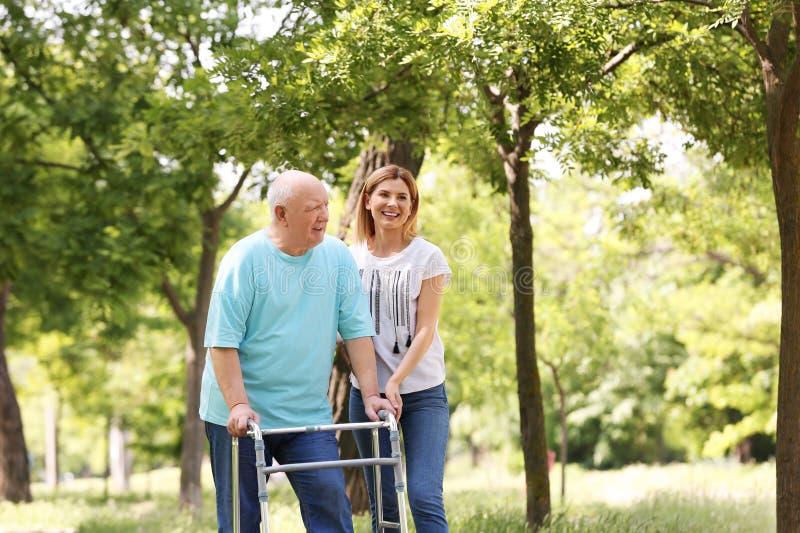 帮助有走的框架的看守者年长人 库存照片