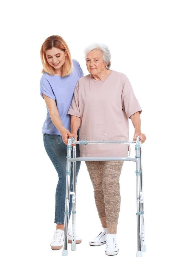 帮助有走的框架的看守者年长妇女在白色 库存图片