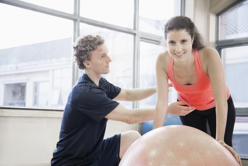 帮助有锻炼的健身教练员少妇在健身球 免版税图库摄影