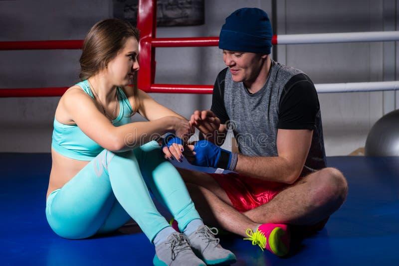 帮助男性运动的拳击手准备绷带运动女性 库存照片