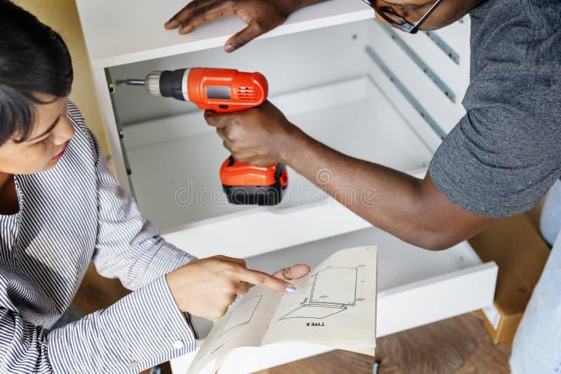 帮助的夫妇在定象碗柜 库存图片