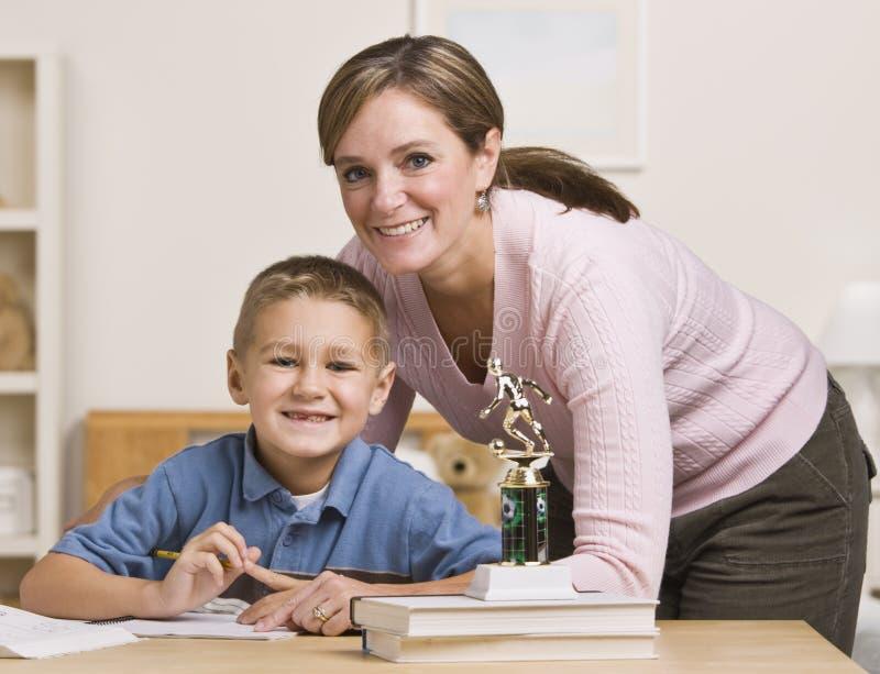 帮助的家庭作业儿子妇女 免版税库存照片