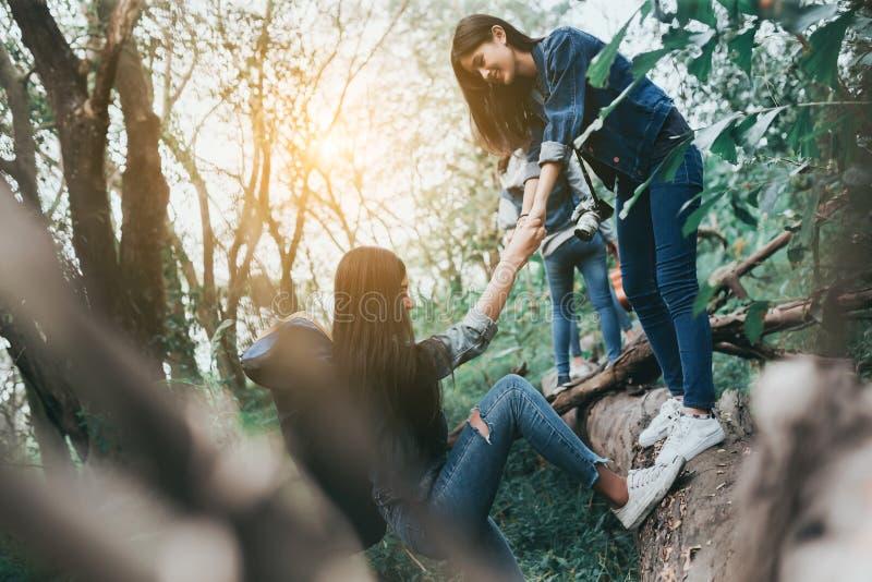 帮助的朋友小组年轻亚裔妇女享受迁徙的旅行 免版税库存图片
