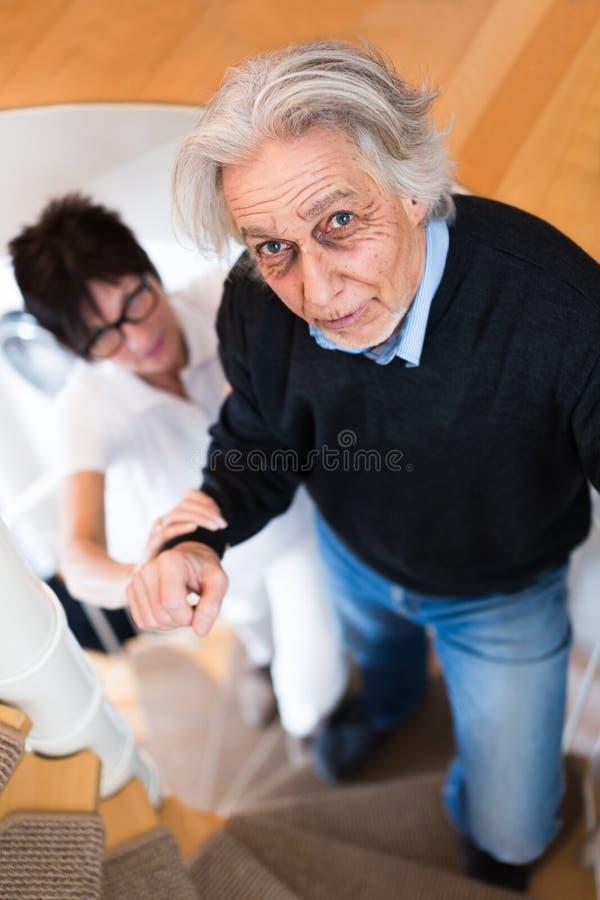 帮助老人上升的台阶的护士 免版税图库摄影