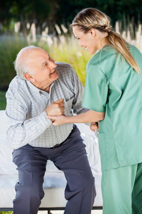 帮助老人的女性护士坐长沙发 库存照片