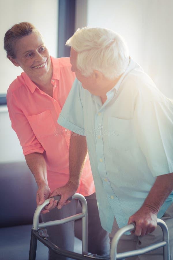 帮助老人的资深妇女走与步行者 库存照片