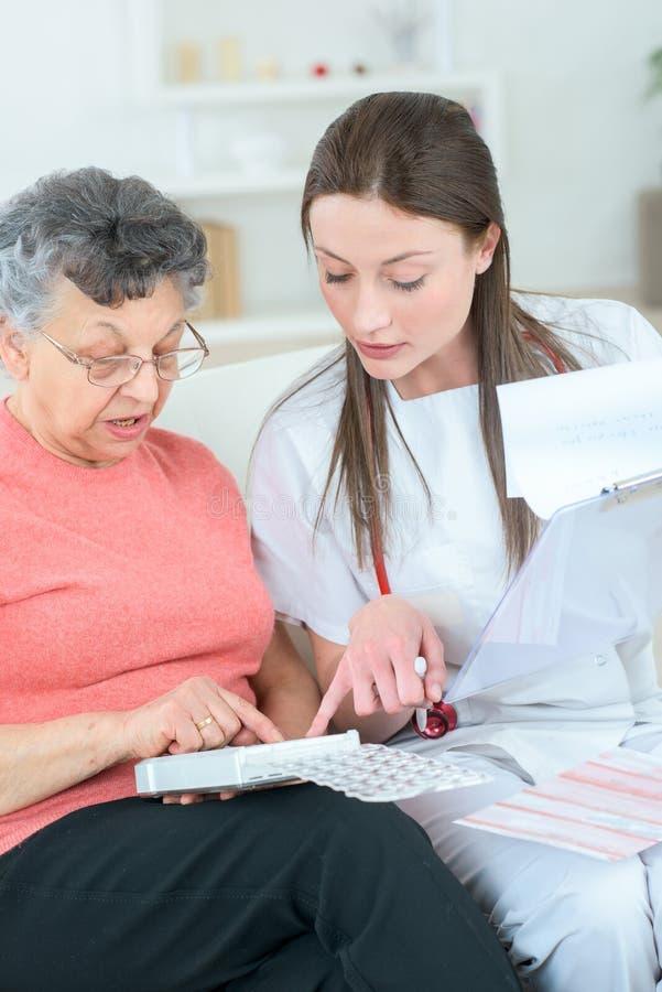 帮助老妇人的家庭参观的护士在治疗之后 免版税库存照片