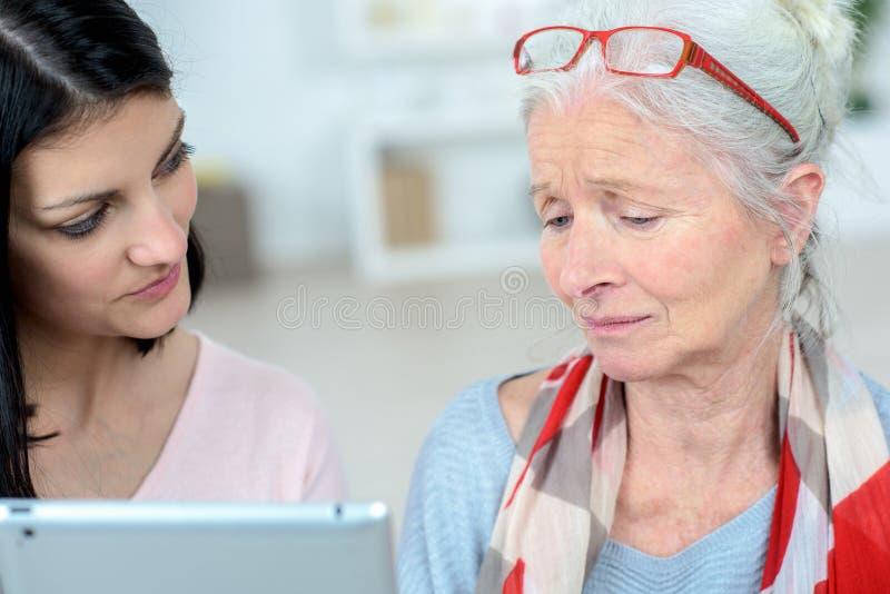 帮助老妇人的护士处理每日任务 免版税图库摄影