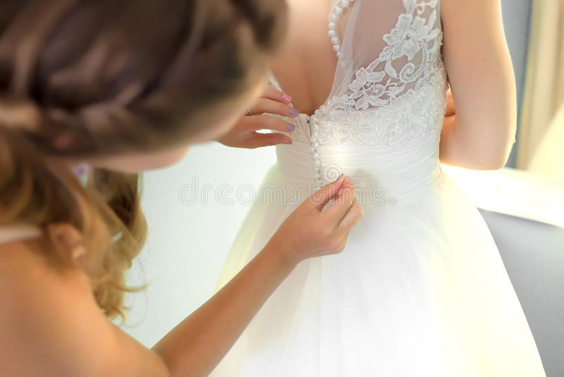 帮助苗条新娘的女傧相系带她婚姻的白色礼服,按在与蓬松裙子的精美鞋带样式在腰部 库存图片