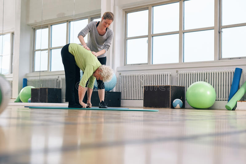 帮助资深妇女的理疗师在健身房 库存图片