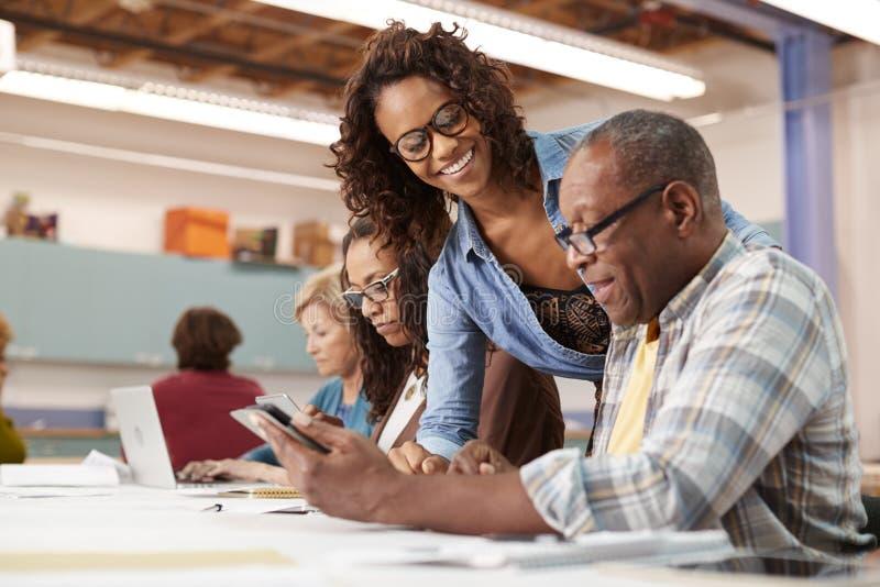 帮助退休的老人的老师在社区活动中心上IT类 免版税库存图片