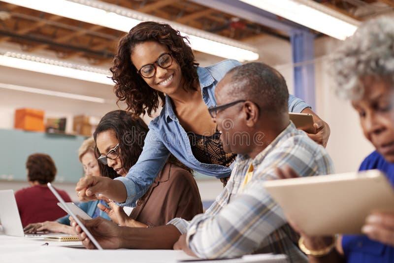 帮助退休的老人的老师在社区活动中心上IT类 库存图片
