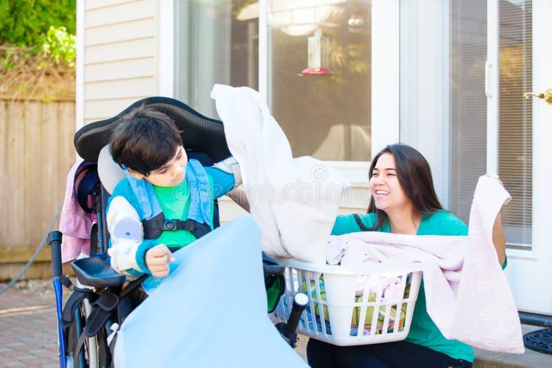 帮助青少年的姐妹折叠洗衣店的轮椅的残疾男孩 免版税库存照片