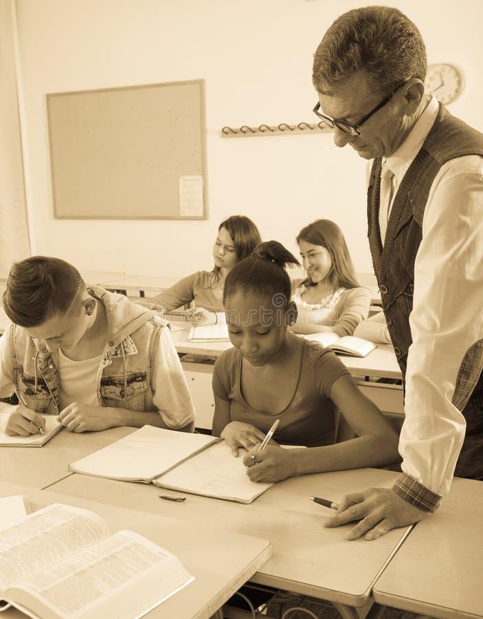 帮助非裔美国人的女小学生的老师 图库摄影