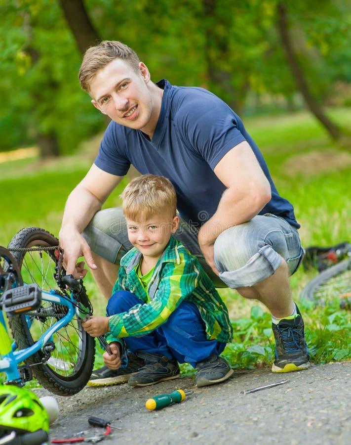 帮助他的儿子固定自行车的父亲 图库摄影