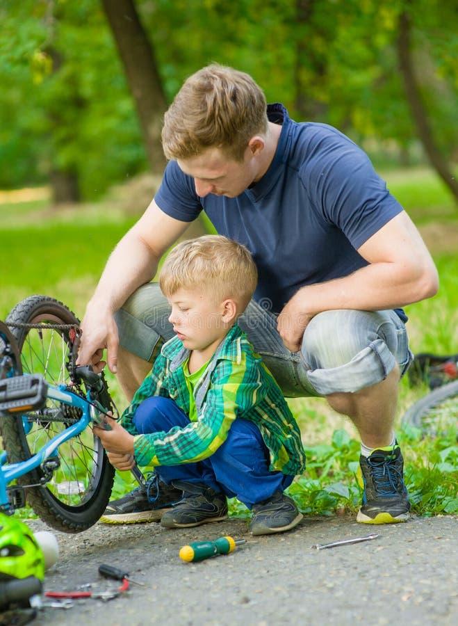 帮助他的儿子固定自行车的父亲 库存照片